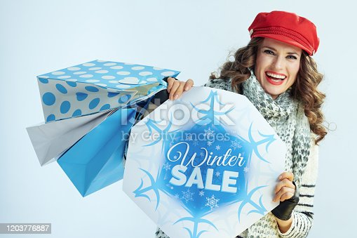 Portrait of happy elegant woman with long brunette hair in sweater, scarf and red hat with shopping bags showing winter sale banner against winter light blue background.