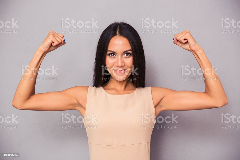 Happy elegant woman showing her biceps stock photo