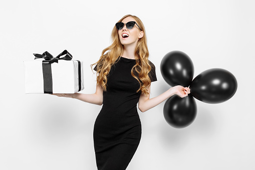 Happy elegant young girl in black dress and sunglasses, happily holding a gift with black Friday ribbon and black balloons on white background. Shopping, discounts, Black Friday