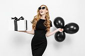 istock Happy elegant young girl in black dress happily holding gift with black Friday ribbon and black balloons on white background 1178219694