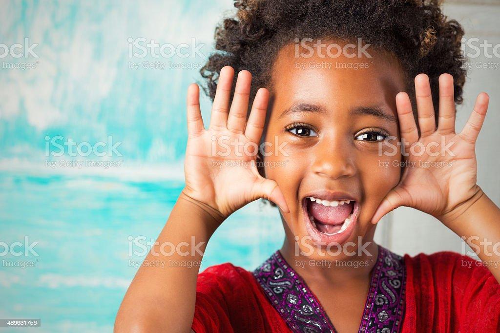 Happy elementary age Ethiopian girl making face at camera stock photo