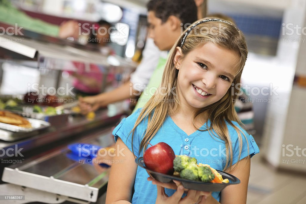 Happy elementary age girl with healthy food in cafeteria line royalty-free stock photo