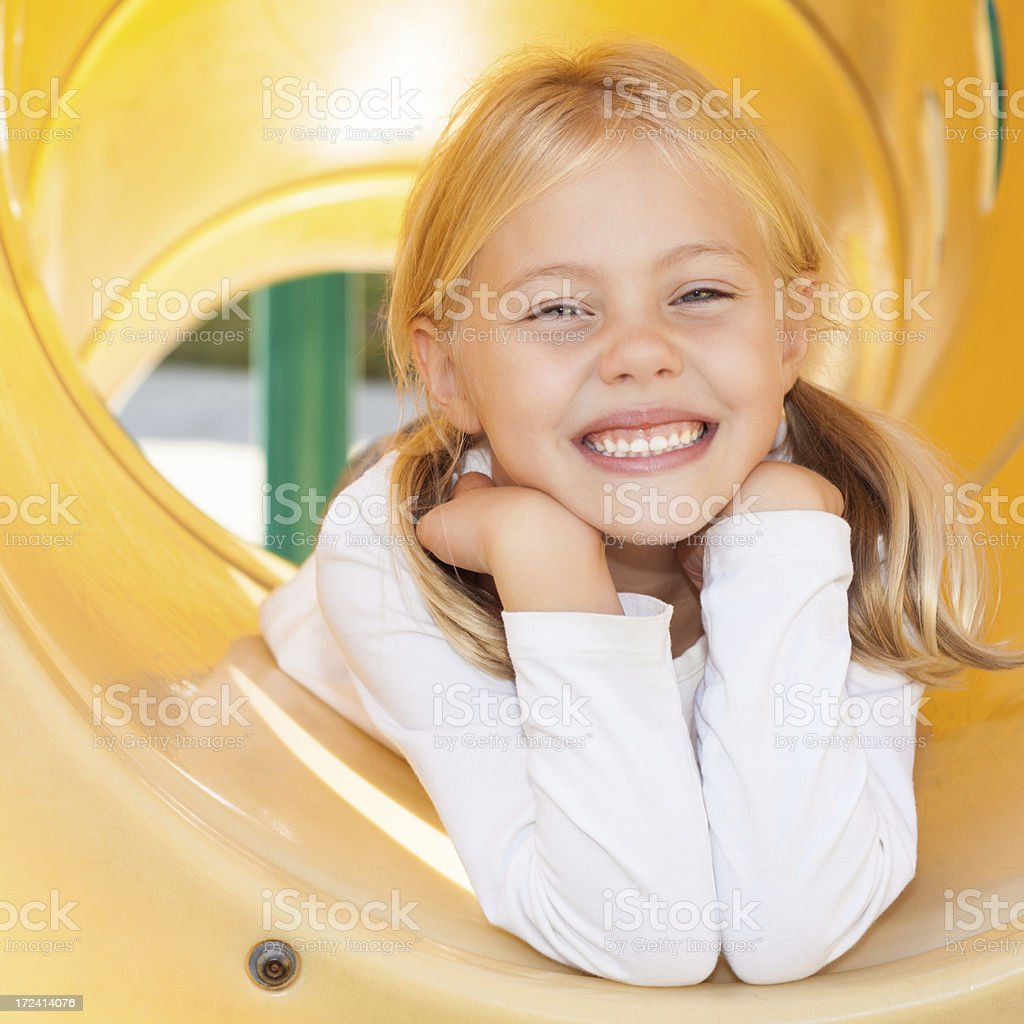 Happy elementary age school girl on playground equipment at recess royalty-free stock photo