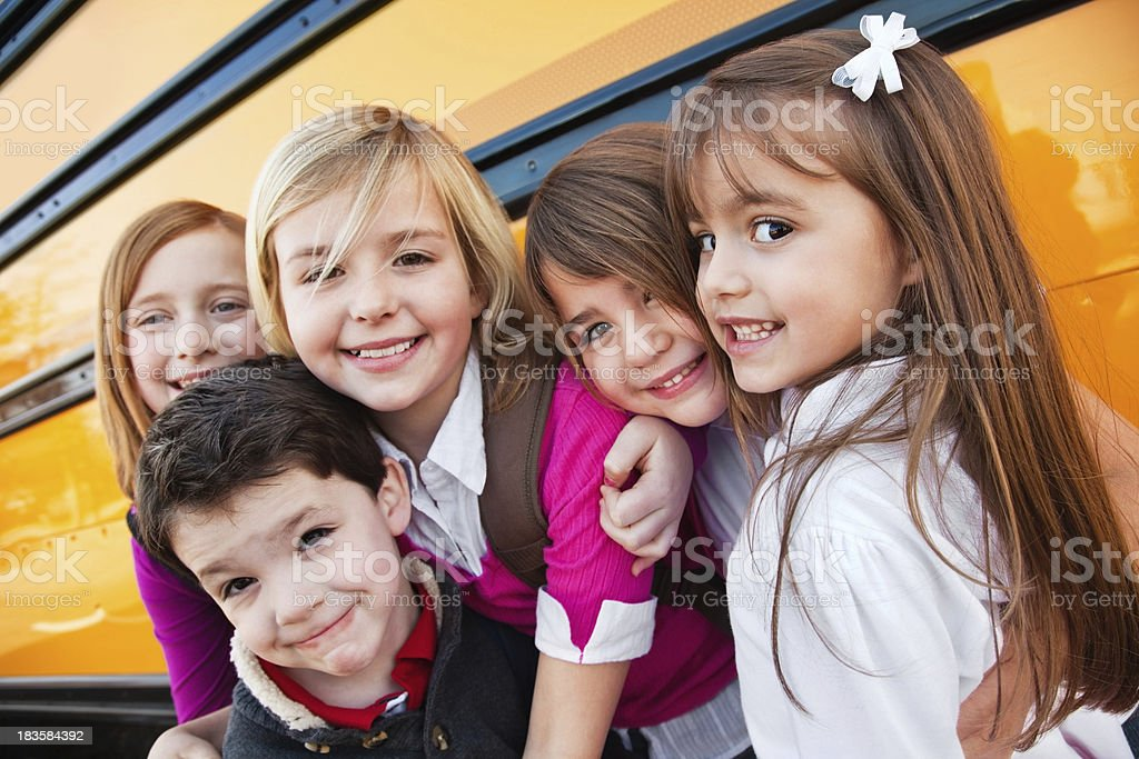 Happy Elementary Aged Friends Close at School Bus royalty-free stock photo