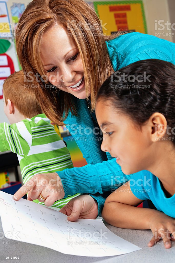 Happy Elementary Girl Receiving Test Paper Back From Teacher royalty-free stock photo
