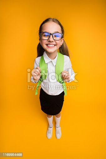 1176772377 istock photo Happy Elementary School Girl In Eyewear Smiling At Camera High-Angle 1169954468