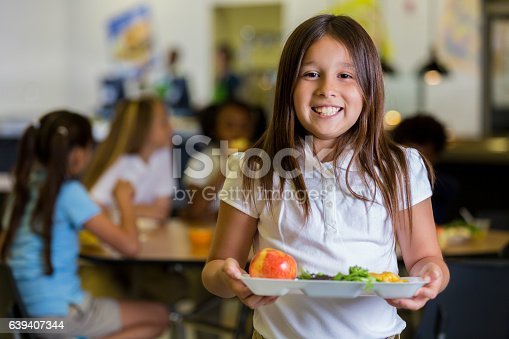 Beautiful Hispanic elementary school girl holds a plate of healthy food in the cafeteria. Her friends are eating at tables in the background. They are wearing school uniforms.