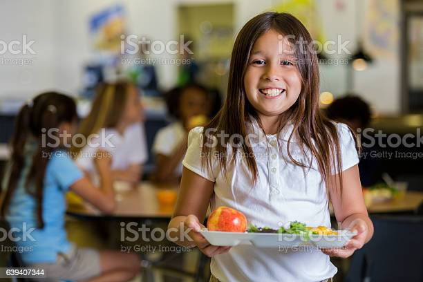 Happy elementary school girl with healthy food in cafeteria picture id639407344?b=1&k=6&m=639407344&s=612x612&h=n 4yon1fm km uvyglh5 wmx4pehirdikxjf2b4ip4a=