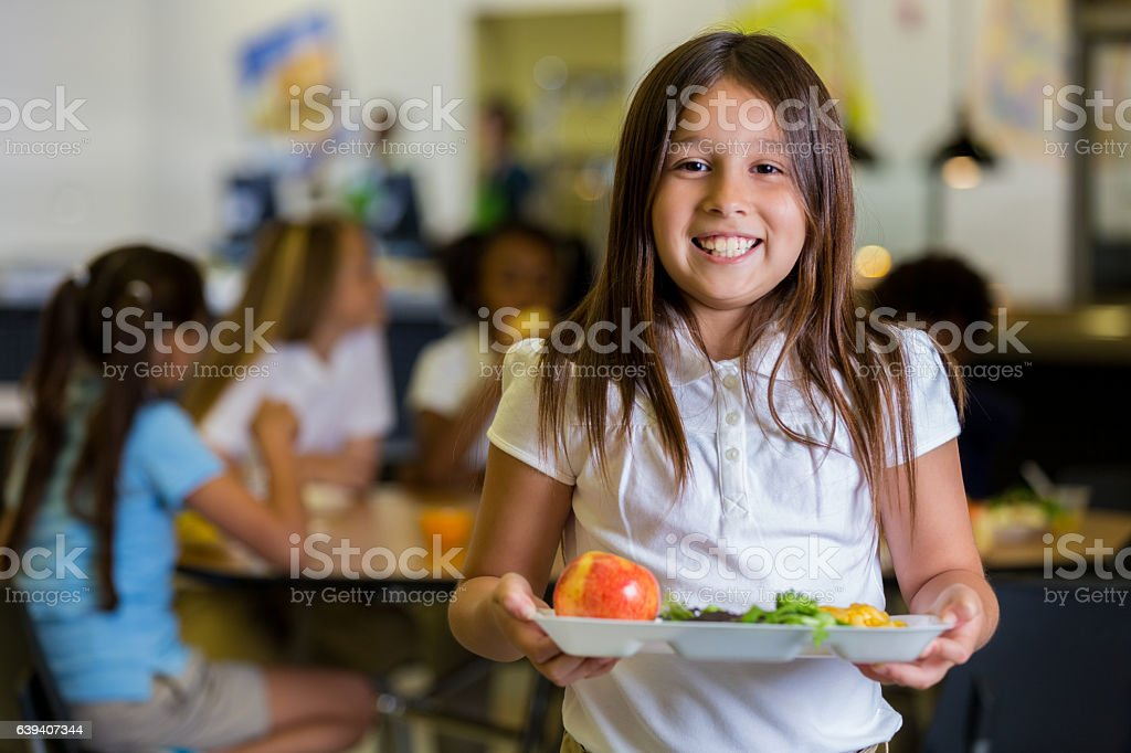 Happy elementary school girl with healthy food in cafeteria stock photo