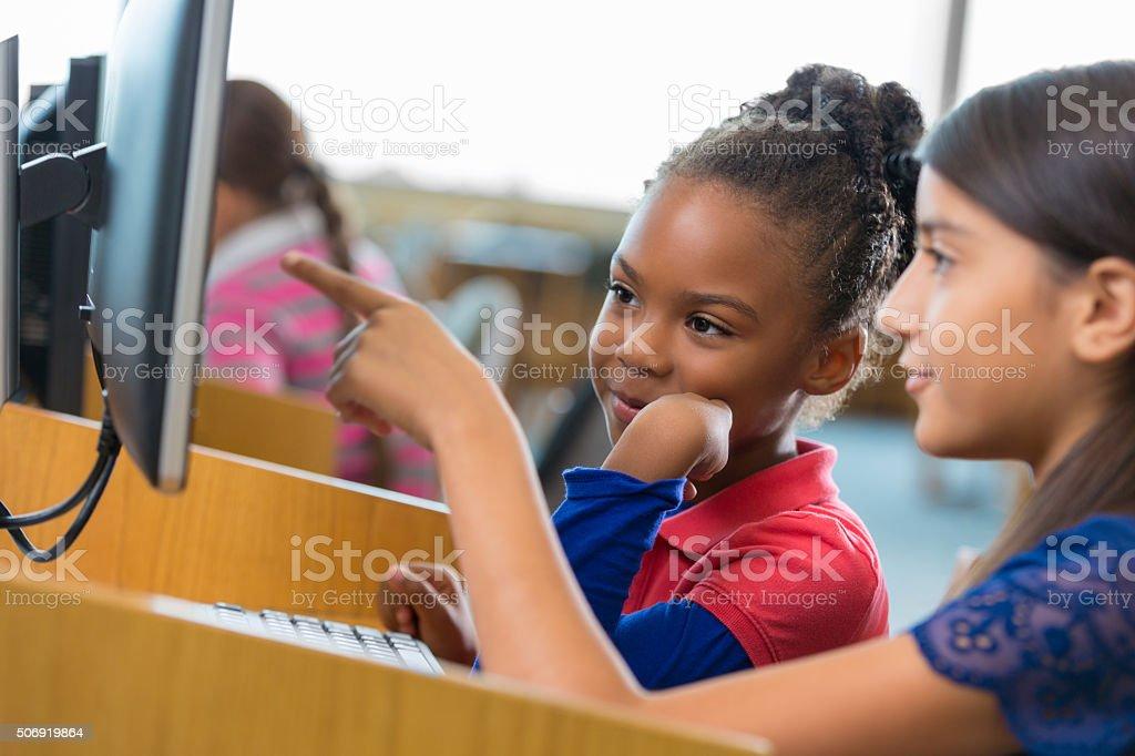 Happy elementary school girls are using a desktop computer stock photo