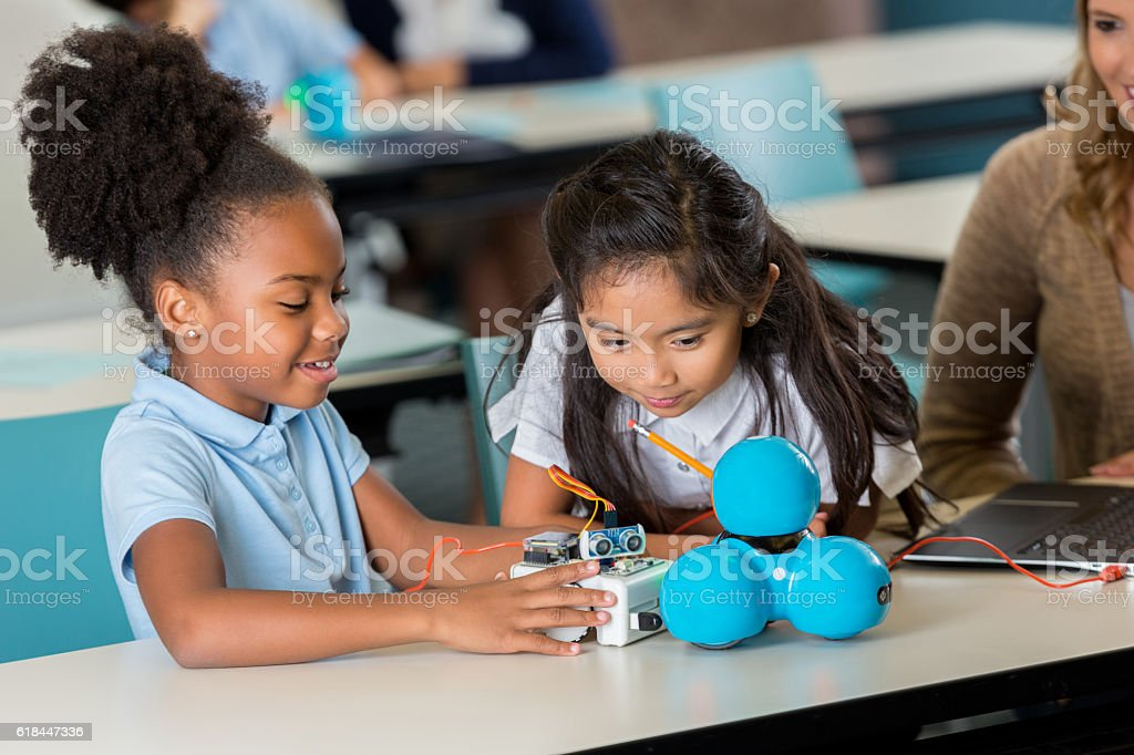 Happy elementary schoolgirls work on robotics project stock photo