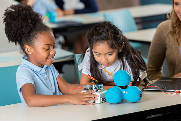 happy elementary schoolgirls work on robotics project - 理科の授業 ストックフォトと画像