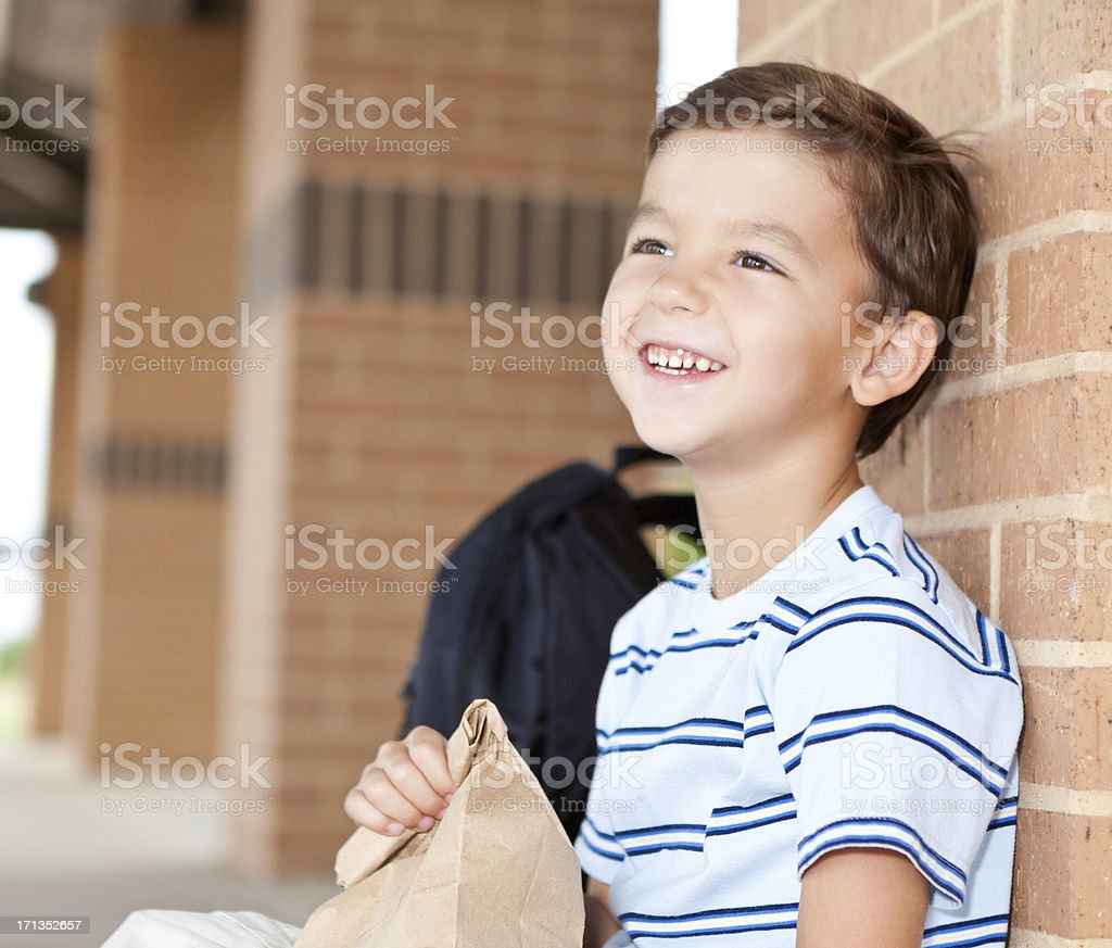 Happy elementary student at school with his lunch bag royalty-free stock photo