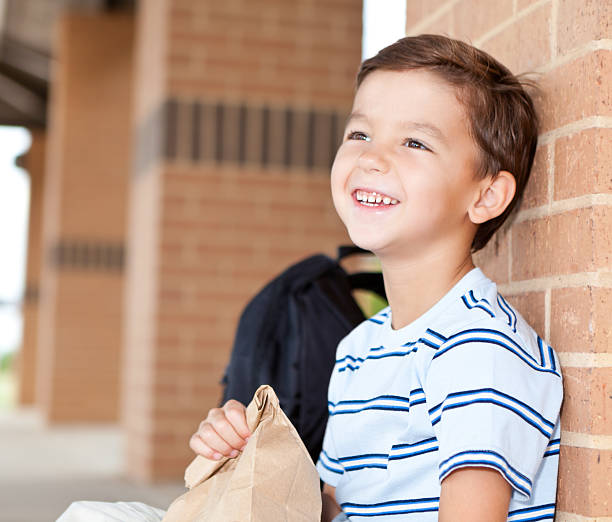 happy elementary student an der schule lunchbox mit seinem - schulkind nur jungen stock-fotos und bilder
