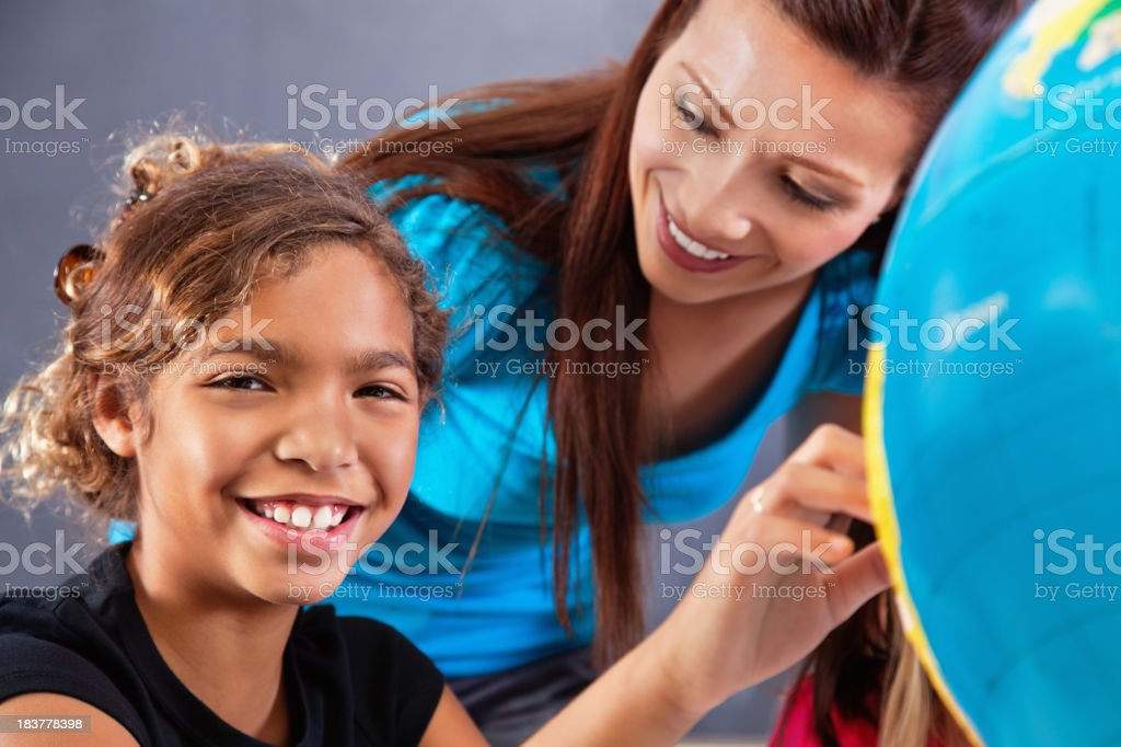 Happy Elementary Student Learning About Geography With Globe in Class royalty-free stock photo