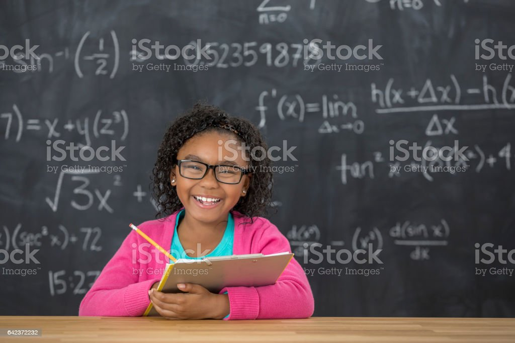 Happy elementary student with glasses in the classroom stock photo