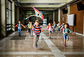 istock Happy elementary students running with a kite in the school hallway. 1142994793