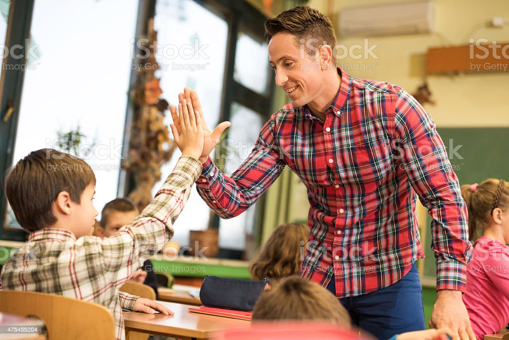 Happy elementary teacher giving high five to his student. stock photo