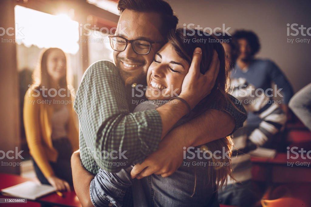 快樂擁抱大學夫婦在教室裡。 - 免版稅一起圖庫照片
