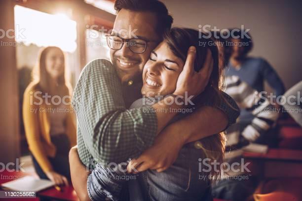 快樂擁抱大學夫婦在教室裡 照片檔及更多 一起 照片