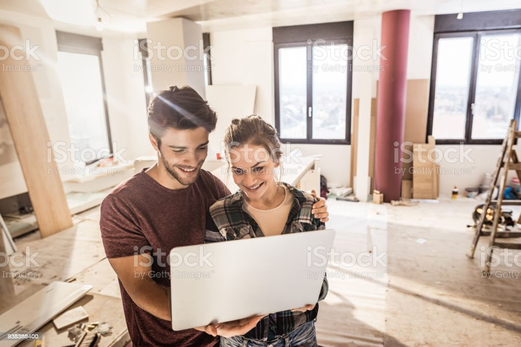 Happy embraced couple using laptop while being on construction site in their apartment. stock photo