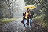Cheerful embraced couple taking a walk on a rainy day at misty forest. Copy space.