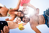 Low angle view of happy family embracing in summer day and looking at camera.