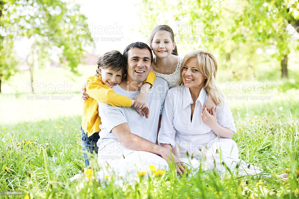 Happy embraced family sitting in the nature. royalty-free stock photo