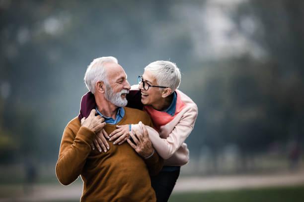 Happy embraced senior couple talking at the park. stock photo