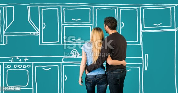 istock Happy embracing couple planning their home kitchen furnishing renovation. 470869156