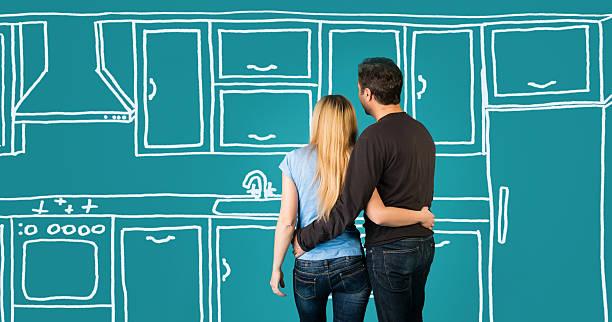 glücklich umarmen paar planung ihres home kitchen einrichtung renoviert. - küche neu gestalten ideen stock-fotos und bilder