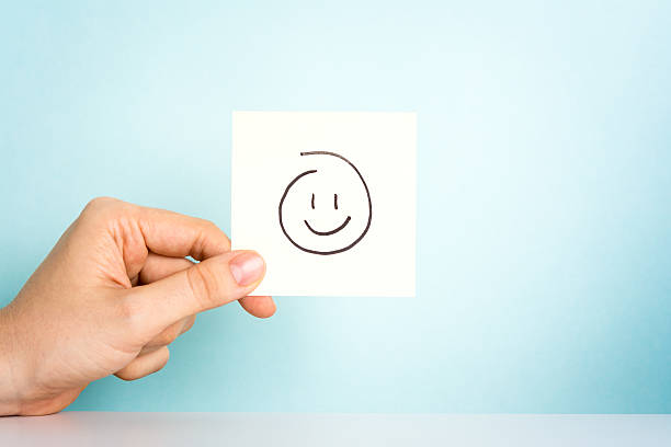happy employee. happy emoticon or icon on blue background. - lustige grußkarten stock-fotos und bilder