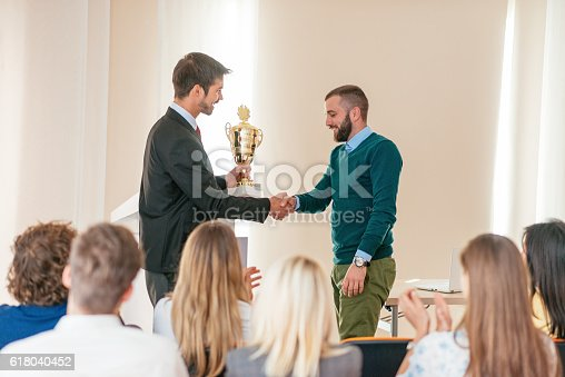 1180918029 istock photo Happy employee of the month receives trophy from manager 618040452