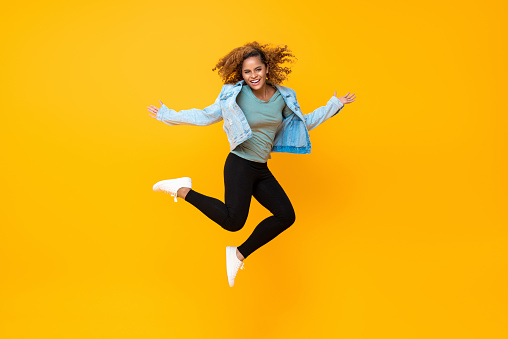 Happy energetic smiling young African-American woman jumping isolated on yellow background