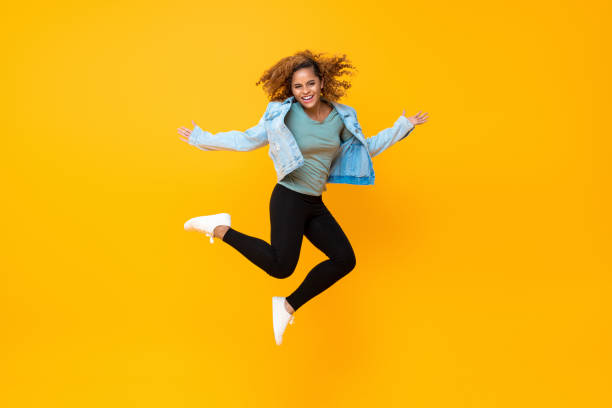 Happy energetic smiling young African-American woman jumping stock photo