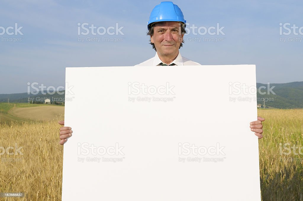 Happy Engineer Holding Blank Billboard.Landscape.Copy Space royalty-free stock photo