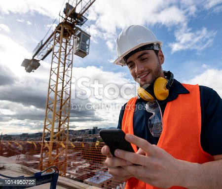 istock Happy engineer texting at a construction site 1014950722