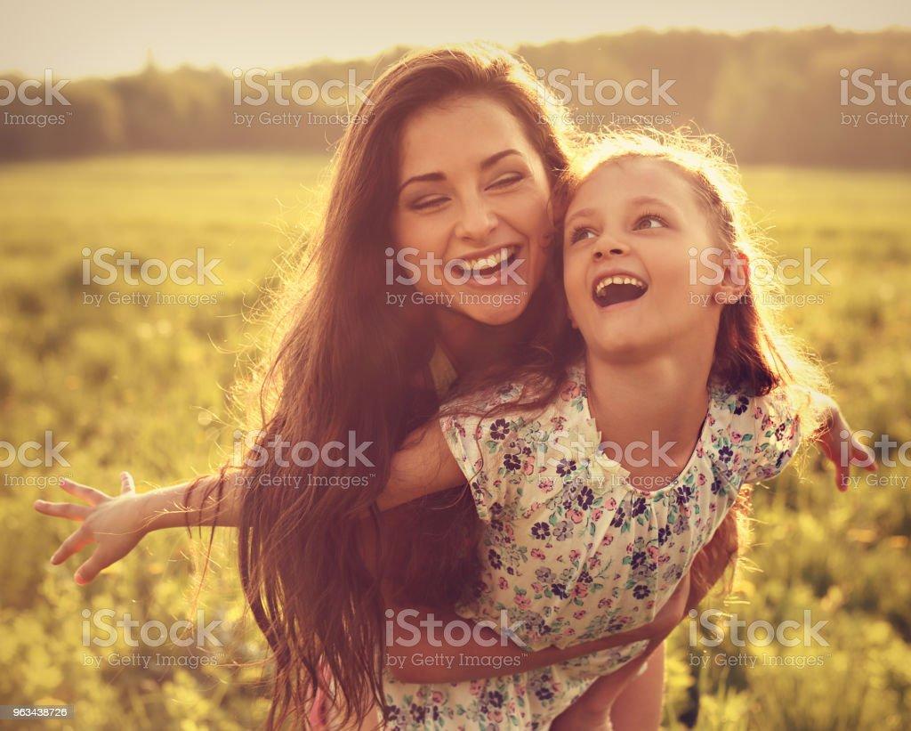 Happy enjoying mother hugging her playful laughing kid girl on sunset bright summer background. Closeup toned portrait - Zbiór zdjęć royalty-free (Córka)