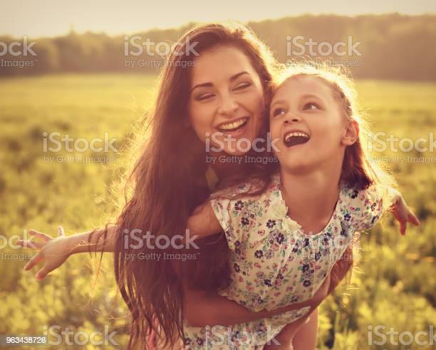 Happy Korzystających Matka Przytulanie Jej Figlarny Śmiejąc Się Dziecko Dziewczyna Na Zachód Słońca Jasne Letnie Tło Zbliżenie Stonowanych Portret - zdjęcia stockowe i więcej obrazów Córka