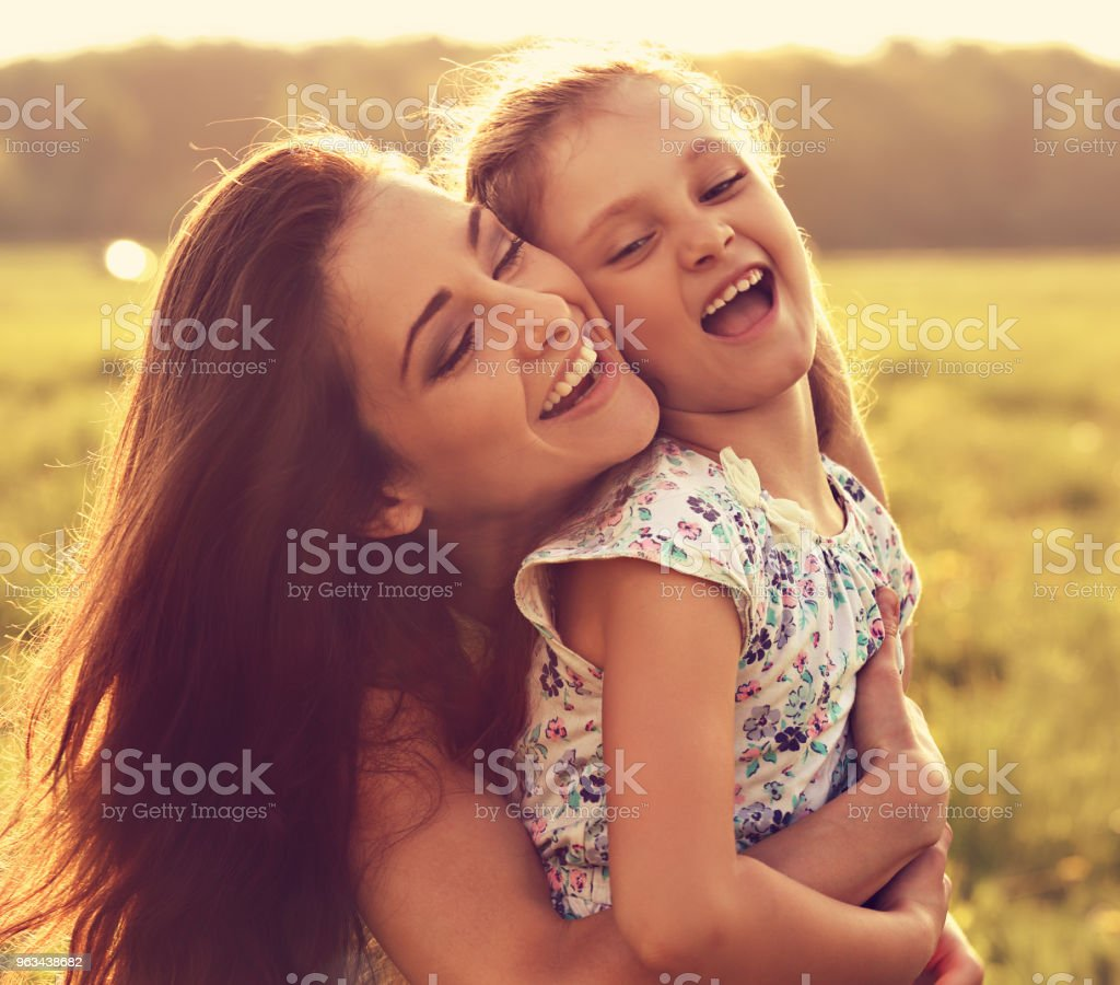 Happy enjoying smiling mother hugging her playful laughing kid girl on sunset bright summer background. Closeup toned portrait - Zbiór zdjęć royalty-free (Córka)