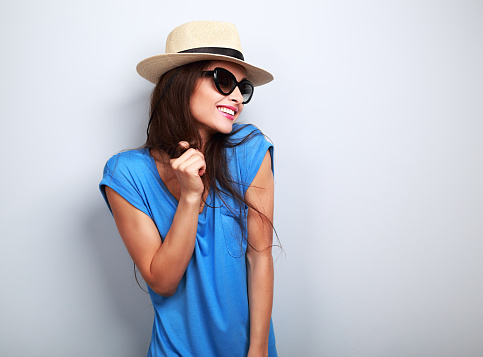Happy enjoyment young woman in sun glasses and hat posing