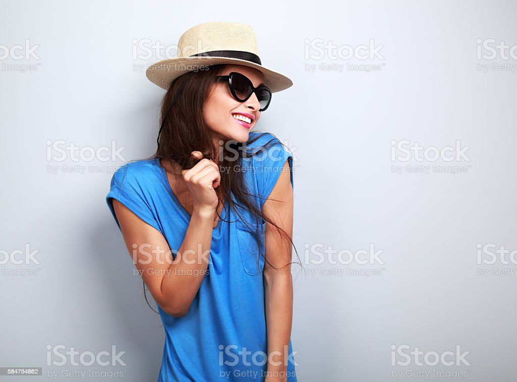 Happy enjoyment young woman in sun glasses and hat posing stock photo