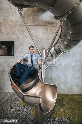 Young carefree businessman having fun while going down the slide in a hallway of an office building.