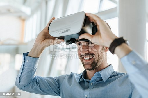 Young happy businessman having fun while using VR headset in the office.
