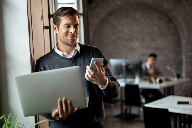 happy entrepreneur texting on smart phone while holding laptop in the office. - surfing the net stock pictures, royalty-free photos & images