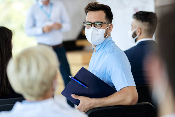 Happy entrepreneur wearing protective face mask while attending business seminar. stock photo