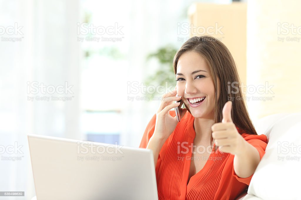 Happy entrepreneur working with thumbs up stock photo