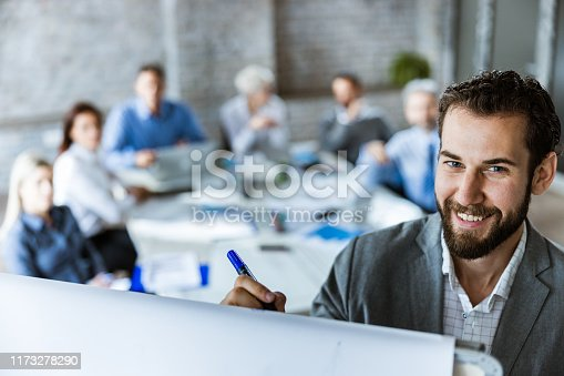 Happy male entrepreneur writing on whiteboard during a business meeting in the office. There are people in the background.