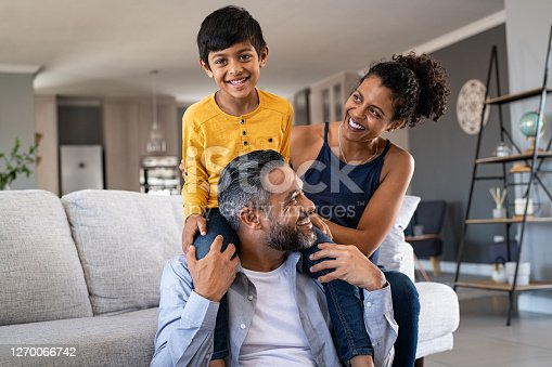 Cheerful african mother and indian father playing with son at home. Cute boy enjoying sitting on father shoulder while looking at camera. Middle eastern family having fun together on the sofa at home.