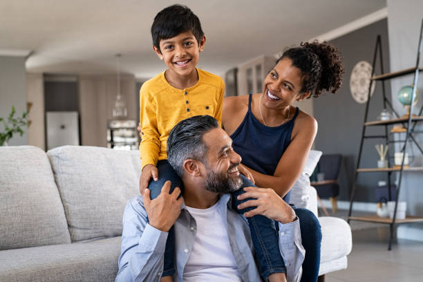 Happy ethnic family playing together at home stock photo